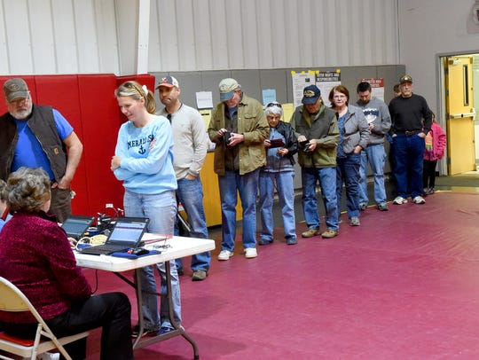 Voters wait in line to be processed to vote at the