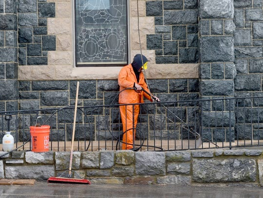 A workman power washes the lower stones on the exterior
