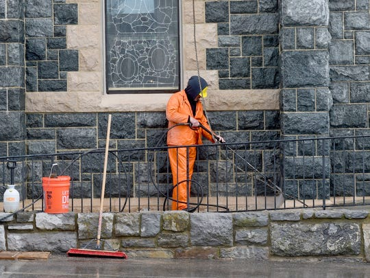 A workman power washes the lower stones on the exterior of St. Francis of Assisi Catholic Church in Staunton on Tuesday, March 15, 2016.