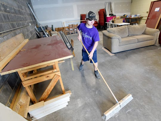 Levi Crawford, 15, of Verona sweeps up in space destined to become a youth center as he volunteers at the Verona Community Center on Monday, March 28, 2016.