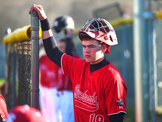 Hand on the fence post in the dugout, Riverheads catcher Forrest Shuey has his mask on his head ready as he watches the action on the field during a baseball game played in Swoope on Tuesday, April 5, 2016.