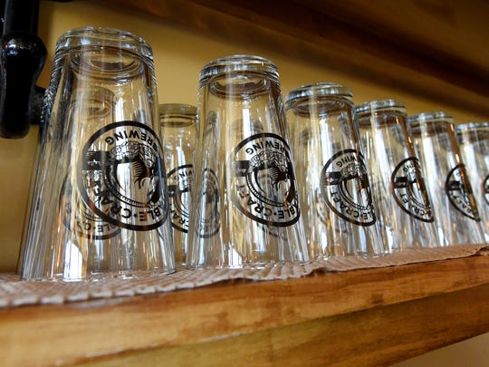 Glasses with the establishment's logo on a shelf in