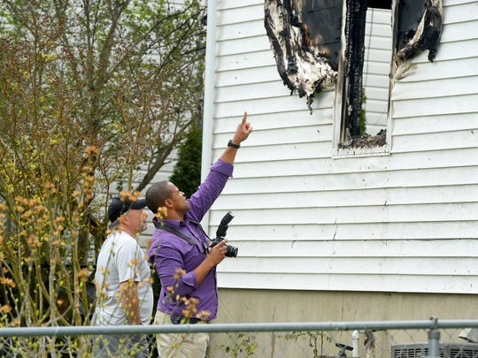 An investigator points towards fire damage while working