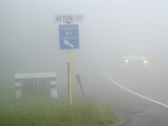 A van is barely visible in the fog on U.S. 250 as it passes a sign pointing the way to the tourist information center on Afton Mountain on Thursday morning, May 12, 2016.