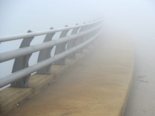 The railing and sidewalk disappears into the fog as the Skyline Drive passes over Interstate 64 on top of Afton Mountain on Thursday morning, May 12, 2016.