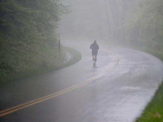 Ray Russell of Boone, N.C., runs through fog and rain