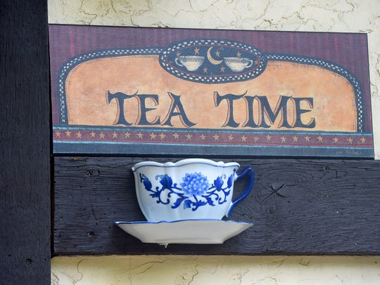 """A sign reads """"Tea Time"""" beside the entrance to the"""