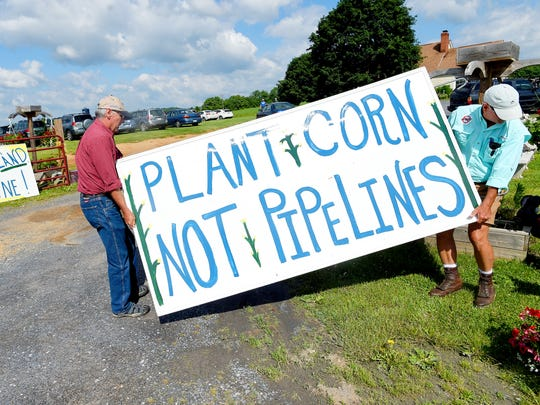 Tom Berlin of West Virginia and Bobby Whitescarver of Swoope position a sign alongside U.S. 340 where people gather for the event. Members of the Cowboy and Indian Alliance visited Stuarts Draft to plant ÒSeeds of Resistance,Ó of corn sacred to the Ponca Nation of Oklahoma, in the path of the proposed Atlantic Coast Pipleline with the help of landowners and others on Monday, June 6, 2016.