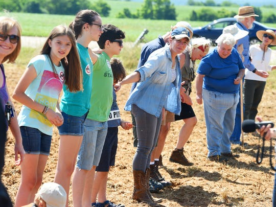 """Jane Kleeb (center), president of Bold Alliance, looks down the line of people gathered to help plant a row of the corn. Members of the Cowboy and Indian Alliance visited Stuarts Draft to plant """"Seeds of Resistance,"""" of corn sacred to the Ponca Nation of Oklahoma, in the path of the proposed Atlantic Coast Pipleline with the help of landowners and others on Monday, June 6, 2016."""