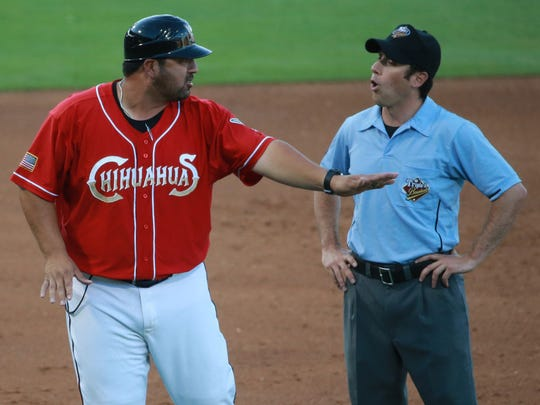 "El Paso manager Rod Barajas and umpire Billy Cunha discuss an ""out"" call at third base Tuesday. An El Paso runner was called out trying to return to third."
