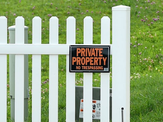 """A """"private property"""" sign is screwed into a fence outside"""