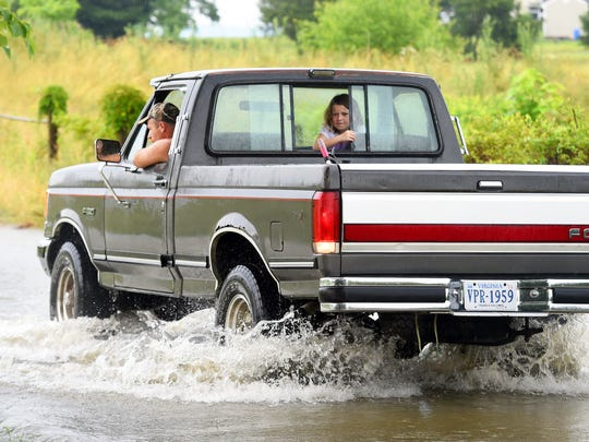 A young girl peaks out the back window as a man drives the truck across a flooded section of Eakle Road in Augusta County following heavy rains on Monday, June 27, 2016.