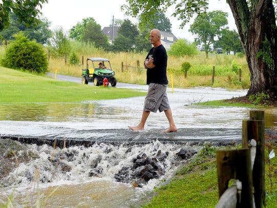 Home owner David Johnson walks across water flowing