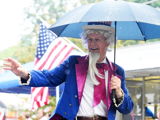 R.M. Stone carries an umbrella to shelter him from the rain and waves to the crowd while portraying Uncle Sam. America's Birthday Celebration held its annual parade in Gypsy Hill Park on Monday, July 4, 2016.