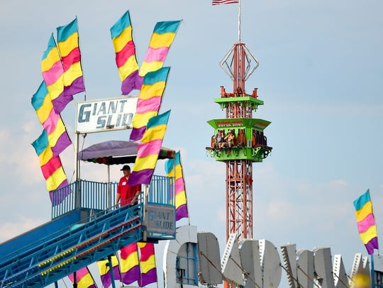 Fair-goers ride the Super Shot on the midway during