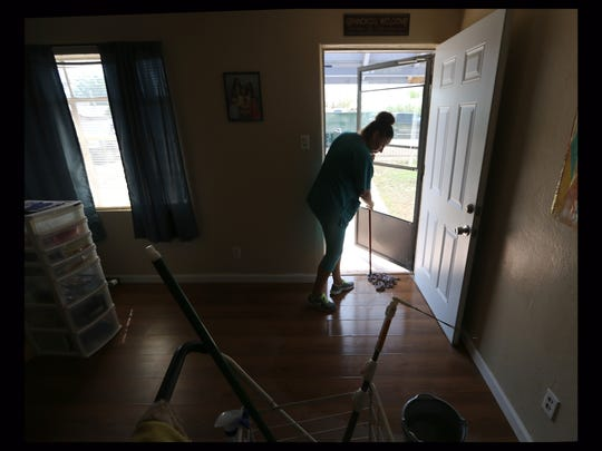 Lorena Medina of Lone Star Maids on Tuesday afternoon mops the floor in Isela Quintero's home on Verde Circle. Mud and water from an adjacent irrigation canal went into the house and other neighboring homes early in the morning. Residents spent all day cleaning up. Quintero said she will not be able to stay there because of the damage.