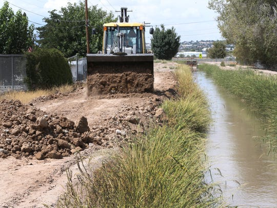 A backhoe on Tuesday positions dirt on the canal banks behind homes on Verde Circle in the Lower Valley.