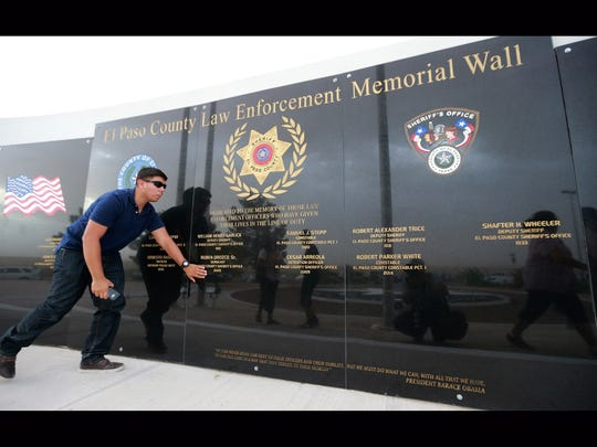 Ruben Orozco, Jr. reached to touch the name of his father, Sheriff's Sgt. Ruben Orozco, Sr. following an unveiling ceremony for the new El Paso County Law Enforcement Memorial Wall.