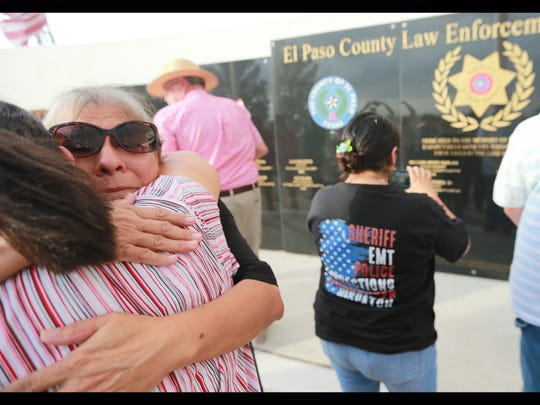 Mary Orozco, widow of sheriff's Sgt. Ruben Orozco, is embraced Tuesday after the unveiling of the new El Paso County Law Enforcement Memorial Wall.