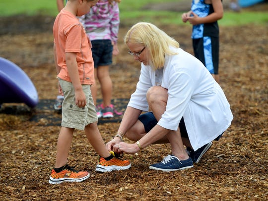 First grade teacher Sherry Liggett ties the shoelace of one of her students during recess on the first day of school on Tuesday, Aug. 9, 2016 at Beverley Manor Elementary School.