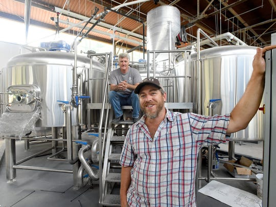 Bart Lanman (right), co-owner of Basic City Beer Co., talks about the final stages of construction as brewmaster Jacque Landry listens while perched on the steps leading up to the brewing tanks. They speak during an interview at the business, located in the old Virginia Metalcrafters building in Waynesboro on Thursday, Aug. 18, 2016. Lanman owns the business with his brother, Chris Lanman.