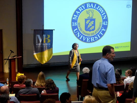Crista Cabe, senior vice president for university relations at Mary Baldwin College, crosses the stage after repositioning one of the banners featuring the school's new brand just prior to the start of  the State of the University address held at the college on Wednesday, Aug. 24, 2016. The college officially changes its name to Mary Baldwin University next week.