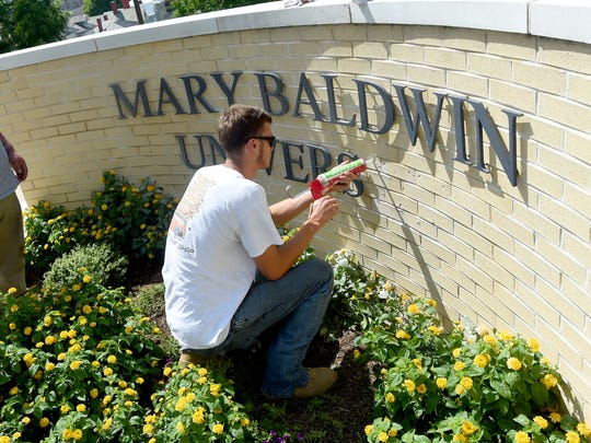 Kirkland Mood of Talley Sign Company installs the last few letters on the sign, now spelling out Mary Baldwin University, at East Frederick and North Coalter streets on Wednesday, Aug. 24, 2016. Mary Baldwin College switches its name to University during a ceremony scheduled for August 31.