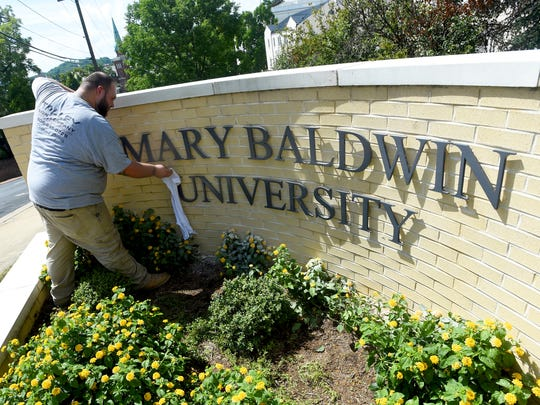Mike Moyer Jr. of Talley Sign Company wipes off the new letters he and a co-worker just finished installing, now spelling out Mary Baldwin University, on a sign at East Frederick and North Coalter streets on Wednesday, Aug. 24, 2016. Mary Baldwin College switches its name to University during a ceremony scheduled for August 31.