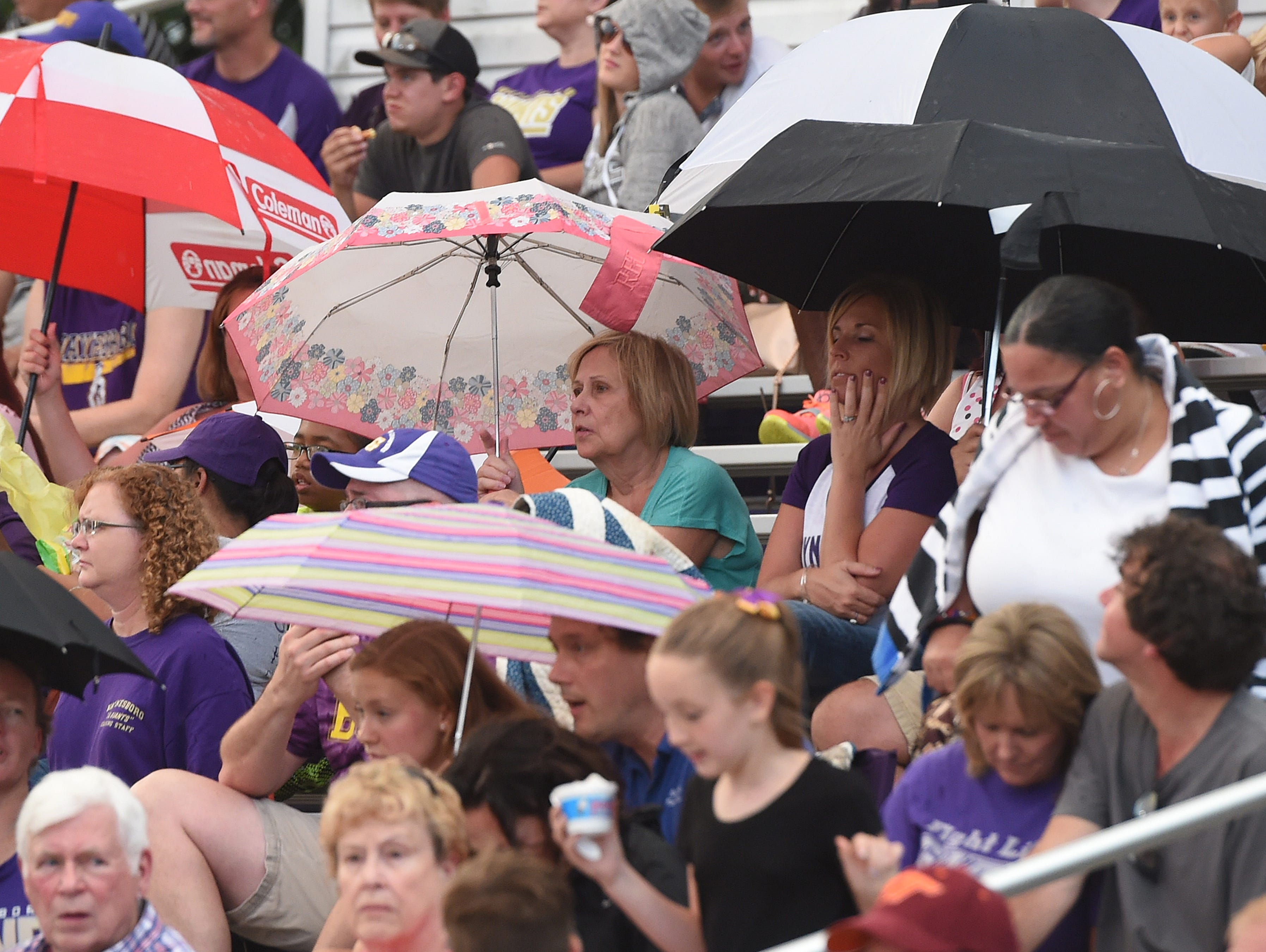 Fans find shelter from the rain that begins to fall using umbrellas during a football game played in Waynesboro on Friday, Aug. 26, 2016.
