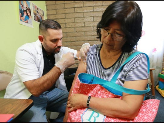 Pharmacist Ray Vasquez administers a flu shot to Raquel