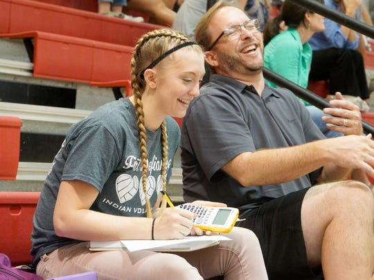 Fort Defiance's Madi Kimmel shares a quick laugh with her father, Scott Kimmel, who sits next to her in the stands. She works on her homework during the junior varsity volleyball game and before her varsity game against Riverheads High School in Greenville on Sept. 8, 2016.