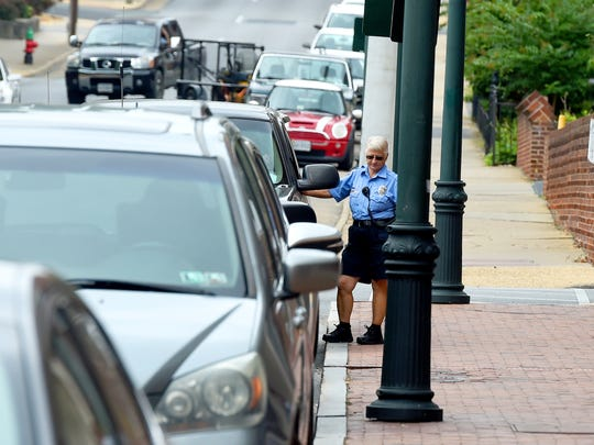"Parking enforcement officer Mary Fitzgerald takes a moment to speak with a driver parked but still in his vehicle while working West Beverley Street. She goes about her job with the Staunton Police Department  on Thursday, Sept. 15, 2016. ""I've been at this for 21 years,"" she says about her time in parking enforcement."