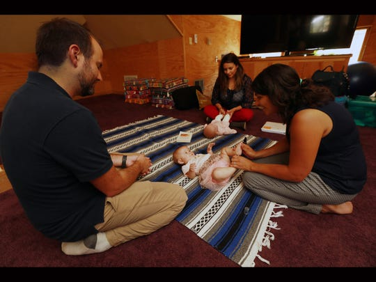 Joshua Graber watches wife Michel Knerl massage daughter Madison Graber's foot Tuesday at The Retreat. Certified Infant massage educator Brenda Amador Schulz demonstrates the technique on a doll.