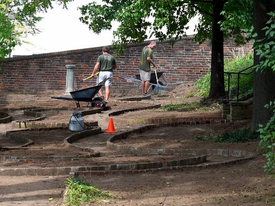 Andrew Davis (center) of the Woodrow Wilson Presidential Library rakes the bare dirt of the boxwood garden at the Presidential Library after the shrubs have all been removed on Wednesday, Sept. 21, 2016. The garden's shrubs were finally removed, with great care after boxwood blight, a fungal disease, wrecked havoc on them last October.