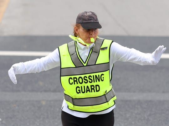 Whistle in her mouth, Dana Totten directs traffic alongside Berkley Glenn Elementary. She works the intersection at Jefferson Avenue and Windsor Road as a school crossing guard with Waynesboro Police Department on Monday, Sept. 26, 2016.