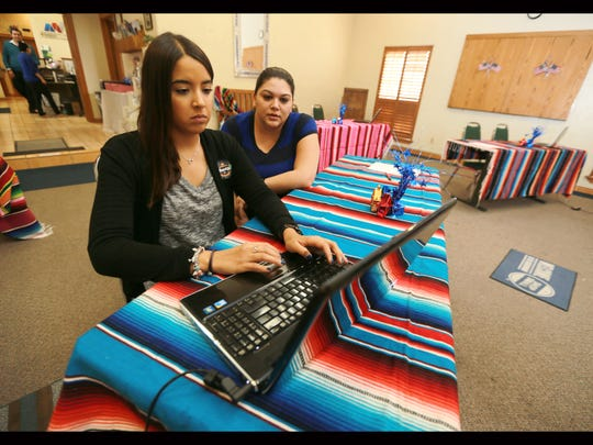 Paulina Lara, left, searched for her name in the list of registered voters Tuesday. She did not find it and then promptly registered to vote at the Hispanic Chamber of Commerce. Michelle Luevano of the Hispanic Chamber of Commerce assisted her.