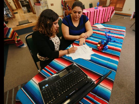 Michelle Luevano of the Hispanic Chamber of Commerce, right, assists Rebeca Rico on Tuesday with registering to vote. The chamber held a voter registration drive which celebrated both National Voter Registration Day and Hispanic Heritage Month.