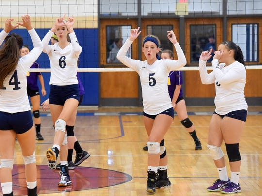 Robert E. Lee's Jennifer Williams and Meghan Wood celebrate a point with teammates on the court during a volleyball match played in Staunton on Thursday, Sept. 29, 2016.