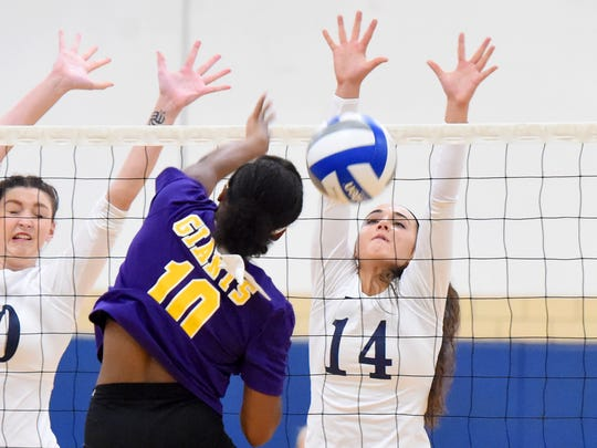 Robert E. Lee's MacKensie Bowles blocks a spike by Waynesboro's Chauncey Johnson at the net during a volleyball match played in Staunton on Thursday, Sept. 29, 2016.