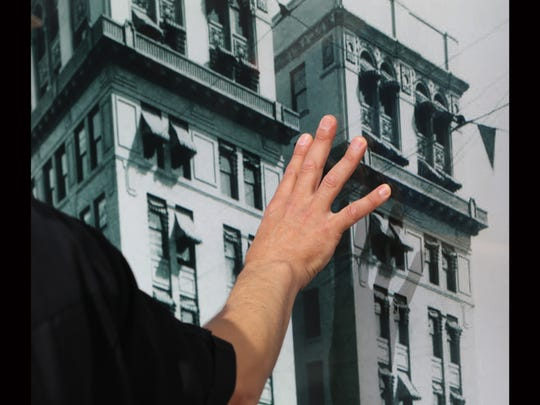 Max Grossman describes a building on a picture in a window at the Plaza building.