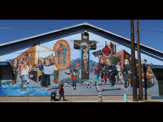 A woman walks past a mural on Father Rahm Drive. The mural features the history of Sacred Heart Church.