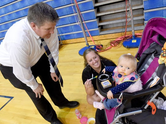 Wendy Hull (center) feeds her one-year-old daughter, Sawyer Hull, as husband Brent Hull talks to their child. They wait for the start of the evening's varsity volleyball match at Fort Defiance High School on Tuesday, Oct. 11, 2016. Wendy currently serves as the assistant coach of Fort Defiance's varsity volleyball team while Brent is a teacher at the school.