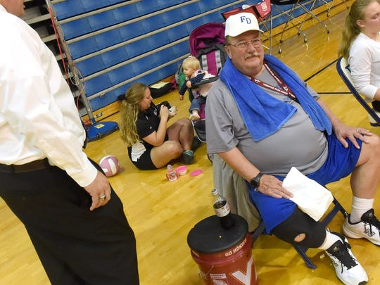 Wendy Hull sits on the floor and feeds her one-year-old daughter, Sawyer Hull, in the background behind her father, Ron Ball, who sits in a chair nearby. They wait for the start of the evening's varsity volleyball match at Fort Defiance High School on Tuesday, Oct. 11, 2016. Wendy currently serves as the assistant coach of Fort Defiance's varsity volleyball team. Ron is a former football coach for Stuarts Draft and Wilson Memorial high schools.