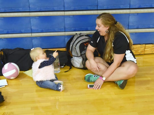 Wendy Hull sits with her 1-year-old daughter, Sawyer Hull, while waiting for the start of the evening's varsity volleyball match at Fort Defiance High School on Tuesday, Oct. 11, 2016. Wendy currently serves as the assistant coach of Fort Defiance's varsity volleyball team.