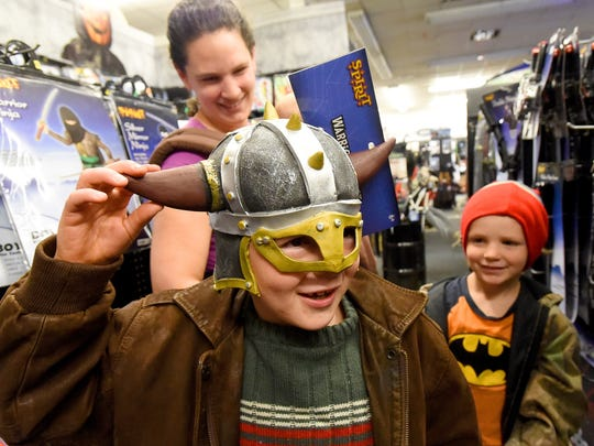 Elijah Rutherford of Nelson County tries on a costume helmet with mother Kate Rutherford and brother Lee Rutherford behind him. They shop at the Spirit Halloween store at Willow Oak Plaza shopping center in Waynesboro on Thursday, Oct. 22, 2015.