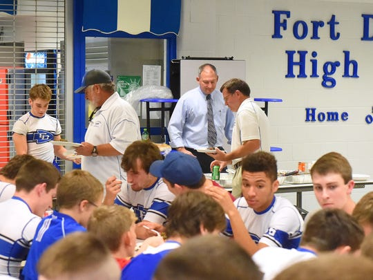 Randy Harris, owner of Super Save Food Market in Weyers Cave, watches as the players eat and the last of the coaches come through the serving line for the varsity football team's pre-game dinner at Fort Defiance High School on Oct. 21, 2016. Harris and his business have been catering the school's meals for about 10 years now.