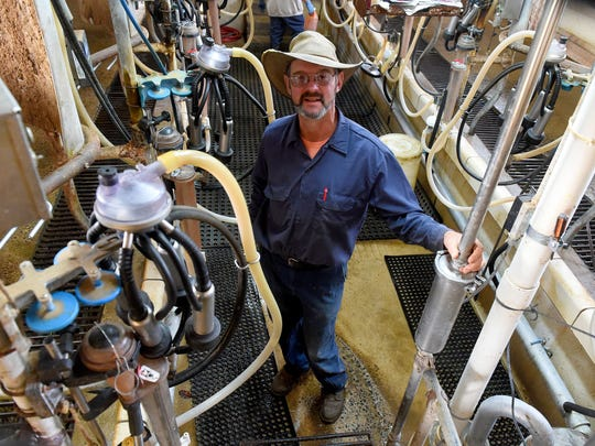 Dairy farmer Kyle Leonard stands in the milking parlor