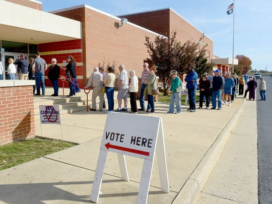 With a line stretching out in front of the school building, a sign points out where to vote at the Greenville voting precinct at Riverheads High School on election day on Tuesday, Nov. 8, 2016.