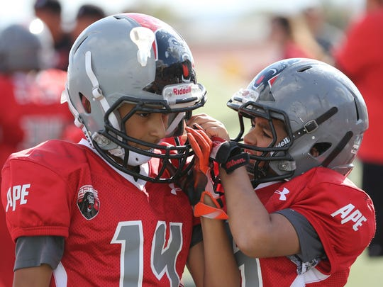 Apes players help each other with their helmets Saturday.