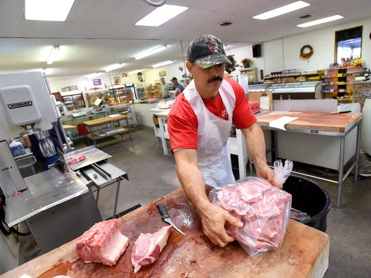 """Everything is ground here on site, fresh daily,"" said John Wood Jr., ""and doesn't come in from out west somewhere pre-packed — packed with whatever they put in it to keep a long shelf life.""  He picks up a bag filled with pork chops to carry over to the scale for pricing before its ready for the customer."